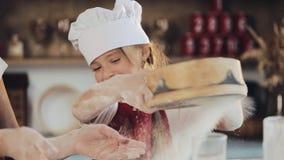 La mamá y la hija en la misma ropa se divierten que prepara una pasta en una cocina acogedora Ellos que preparan las galletas de  metrajes