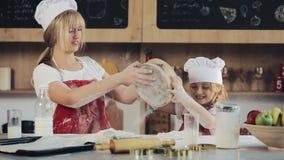 La mamá y la hija en la misma ropa se divierten que prepara una pasta en una cocina acogedora Ellos que preparan las galletas de  almacen de video