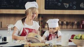 La mamá y la hija en la misma ropa se divierten que prepara una pasta en una cocina acogedora Ellos que preparan las galletas de  almacen de metraje de vídeo
