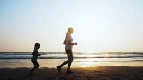 La mamá y la hija están activando en la playa del arena de mar en la puesta del sol almacen de metraje de vídeo