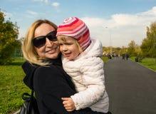 La mamá y la hija están caminando en el parque fotografía de archivo