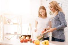 La mamá y la hija están cocinando juntas en la cocina imagen de archivo libre de regalías