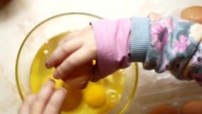 La mamá y la hija están cocinando los huevos revueltos en la cocina