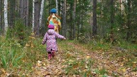 La mamá y la hija están corriendo a lo largo de la trayectoria en el bosque metrajes