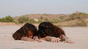 La mamá y la hija están haciendo ejercicio de relajación en la playa de la arena metrajes