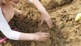 La mamá y la hija están jugando en la playa, construyendo un castillo de la arena D?a asoleado del verano Vacaciones metrajes