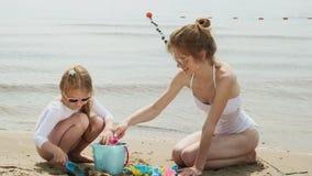 La mamá y la hija están jugando en la playa, construyendo un castillo de la arena D?a asoleado del verano Vacaciones almacen de video
