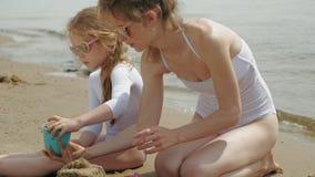 La mamá y la hija están jugando en la playa, construyendo un castillo de la arena D?a asoleado del verano Vacaciones almacen de metraje de vídeo