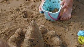 La mamá y la hija están jugando en la playa, construyendo un castillo de la arena D?a asoleado del verano Vacaciones Tiroteo a?re metrajes