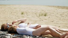 La mamá y la hija están tomando el sol en la playa D?a asoleado del verano almacen de video