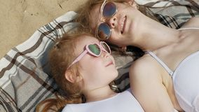 La mamá y la hija están tomando el sol en la playa D?a asoleado del verano almacen de metraje de vídeo
