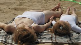 La mamá y la hija están tomando el sol en la playa D?a asoleado del verano metrajes