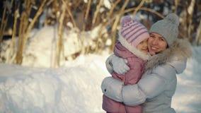 La mamá y la hija felices abrazan en los suburbios en invierno almacen de video
