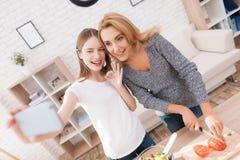 La mamá y la hija hacen el selfie, cocinando juntas en la cocina fotografía de archivo libre de regalías