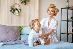 La mamá y la hija hacen un maquillaje el uno al otro, relación de familia feliz imagenes de archivo