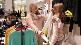 La mamá y la hija intentan encendido la ropa en la tienda metrajes
