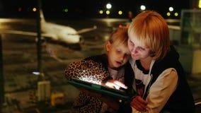 La mamá y la hija juegan en la tableta en el aeropuerto Última tarde, el avión de pasajeros es visible fuera de la ventana almacen de video