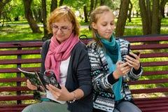 La mam? y la hija leyeron una revista en el parque imágenes de archivo libres de regalías