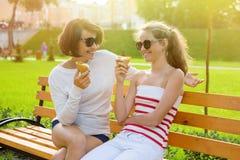 La mamá y la hija ríen, comen el helado foto de archivo libre de regalías