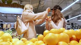 La mamá y la hija se están divirtiendo con las naranjas metrajes