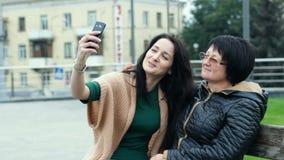 La mamá y la hija se están divirtiendo junto mientras que hace selfies en un smartphone Una mujer adulta representa los cuernos e metrajes