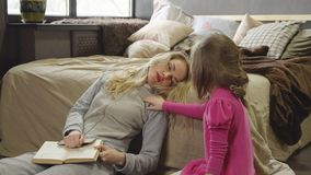 La mamá y la hija se están sentando en el piso al lado de la cama con un libro imagenes de archivo