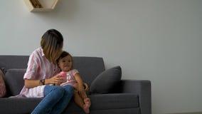 La mamá y la hija se están sentando en el sofá almacen de video