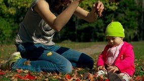 La mamá y la hija se sientan en el otoño en la hierba y el juego con las hojas rojas y amarillas caidas almacen de video