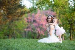 La mamá y la hija son dos años que se sientan en la hierba en el p Imagen de archivo libre de regalías