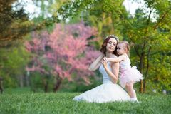 La mamá y la hija son dos años que se sientan en la hierba en el p Fotografía de archivo libre de regalías
