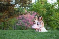 La mamá y la hija son dos años que se sientan en la hierba en el p Fotos de archivo