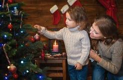 La mamá y la hija visten para arriba un árbol de navidad Foto de archivo libre de regalías