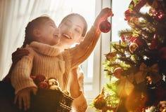 La mamá y la hija adornan el árbol de navidad foto de archivo
