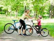 La mamá y la hija dan el alto cinco mientras que completa un ciclo en el parque Fotos de archivo
