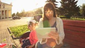 La mamá y la hija de la cámara lenta se están sentando en un banco al lado del camino en la puesta del sol almacen de video