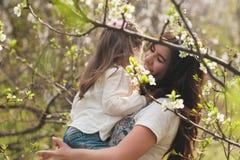 La mamá y la hija del retrato son de abrazo y sonrientes al aire libre, familia, maternidad, niño imagen de archivo libre de regalías