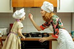 La mamá y la hija en los sombreros blancos del cocinero cocinan en la cocina Fotos de archivo