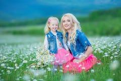 La mamá y la hija en una comida campestre en la manzanilla colocan Dos blondes hermosos que llevan la chaqueta de los vaqueros y  Foto de archivo libre de regalías