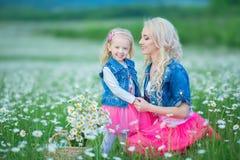 La mamá y la hija en una comida campestre en la manzanilla colocan Dos blondes hermosos que llevan la chaqueta de los vaqueros y  Imagen de archivo libre de regalías