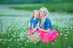 La mamá y la hija en una comida campestre en la manzanilla colocan Dos blondes hermosos que llevan la chaqueta de los vaqueros y  Fotografía de archivo