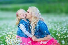 La mamá y la hija en una comida campestre en la manzanilla colocan Dos blondes hermosos que llevan la chaqueta de los vaqueros y  Imágenes de archivo libres de regalías