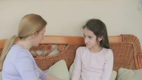La mamá y la hija hablan sincero en casa en un sofá de mimbre metrajes