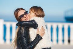 La mamá y la hija pasan tiempo que caminan cerca del mar Foto de archivo