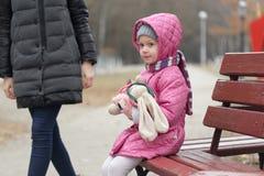 La mamá y la hija se están sentando en un banco de parque imagen de archivo libre de regalías