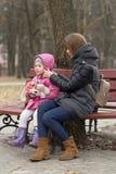La mamá y la hija se están sentando en un banco de parque fotos de archivo libres de regalías