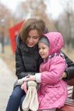 La mamá y la hija se están sentando en un banco de parque fotografía de archivo libre de regalías