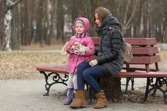 La mamá y la hija se están sentando en un banco de parque imágenes de archivo libres de regalías