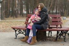 La mamá y la hija se están sentando en un banco de parque fotos de archivo