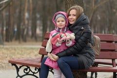 La mamá y la hija se están sentando en un banco de parque foto de archivo
