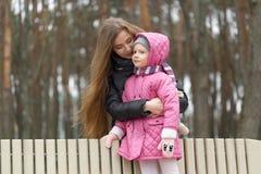 La mamá y la hija se están sentando en un banco de parque foto de archivo libre de regalías